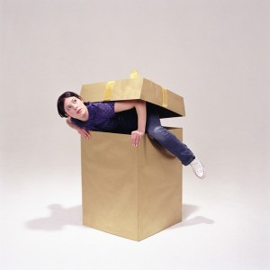 Young woman climbing out of box